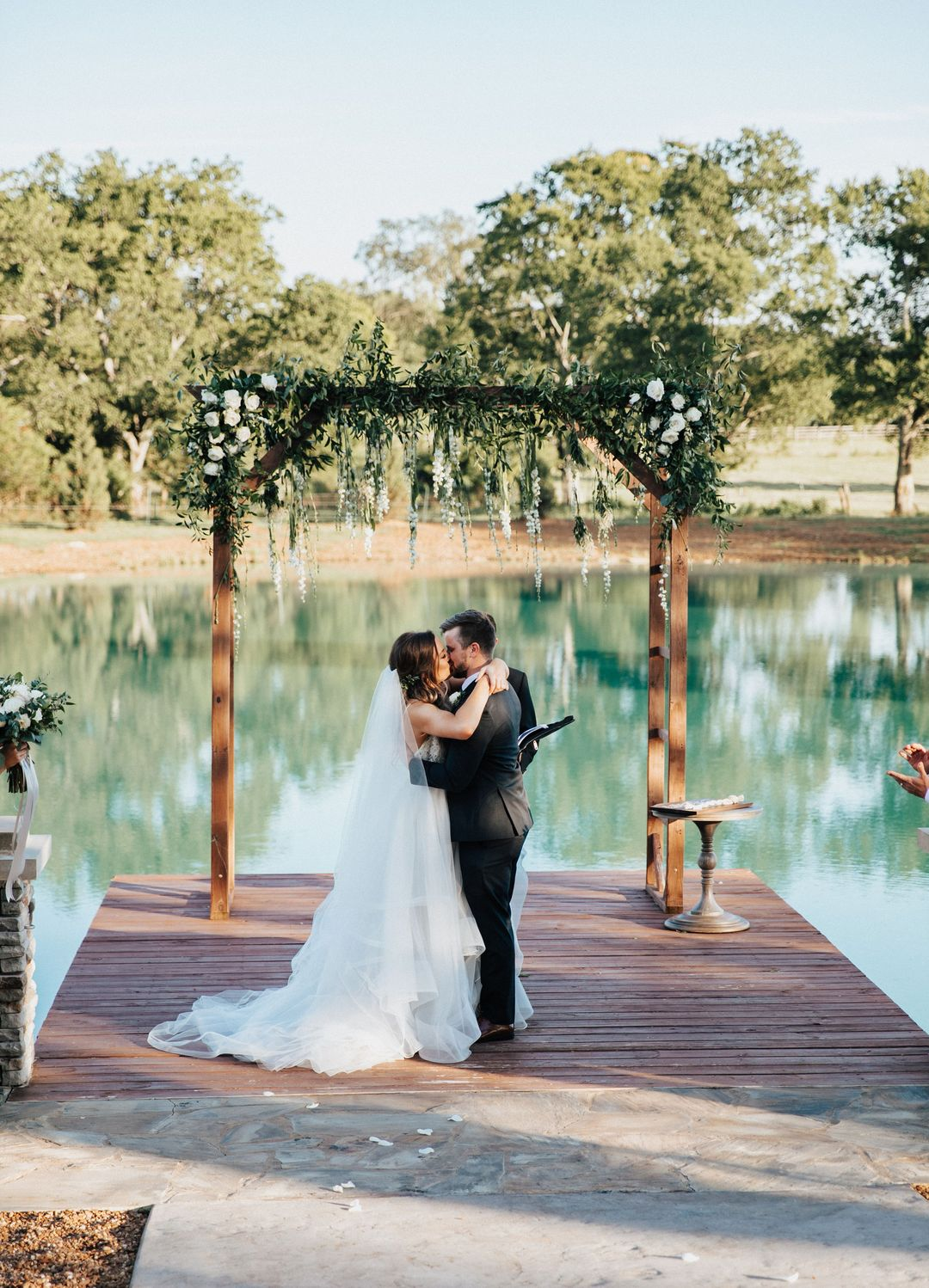 wedding ceremony outdoors, bride and groom kiss