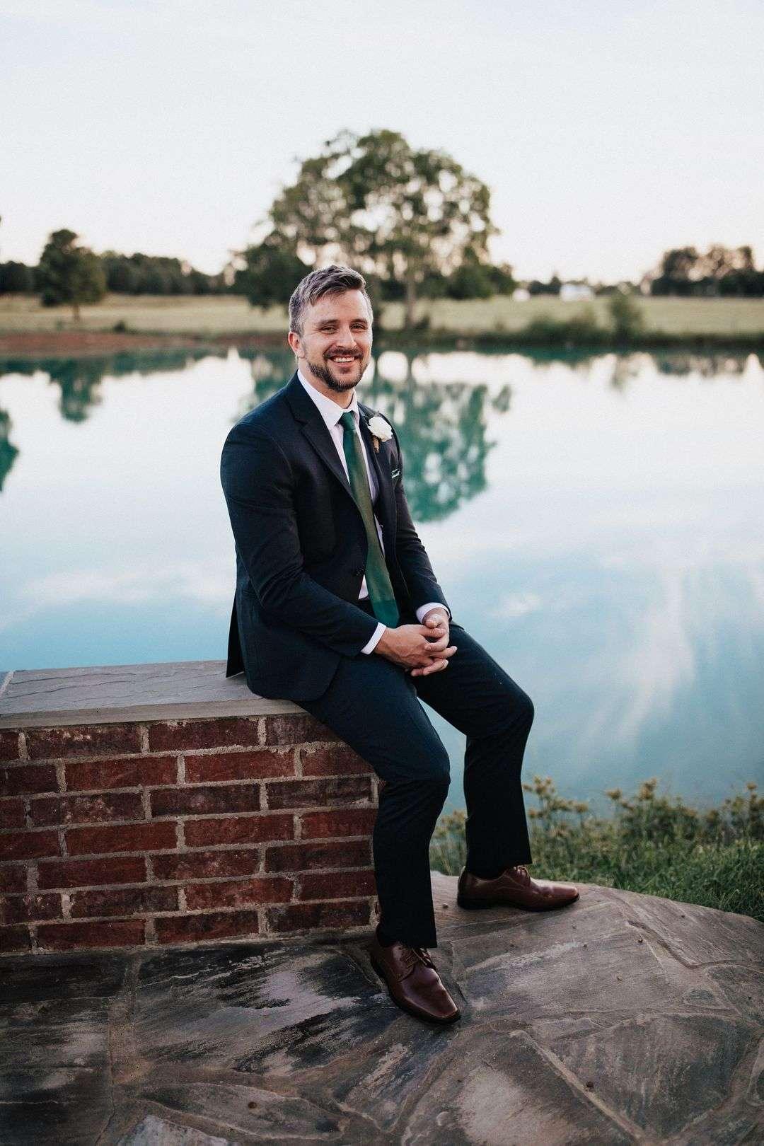 groom portraits, black groom tux and green tie, white boutonierre