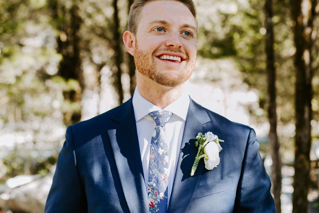 groom in a navy suite with white boutonniere and floral tie