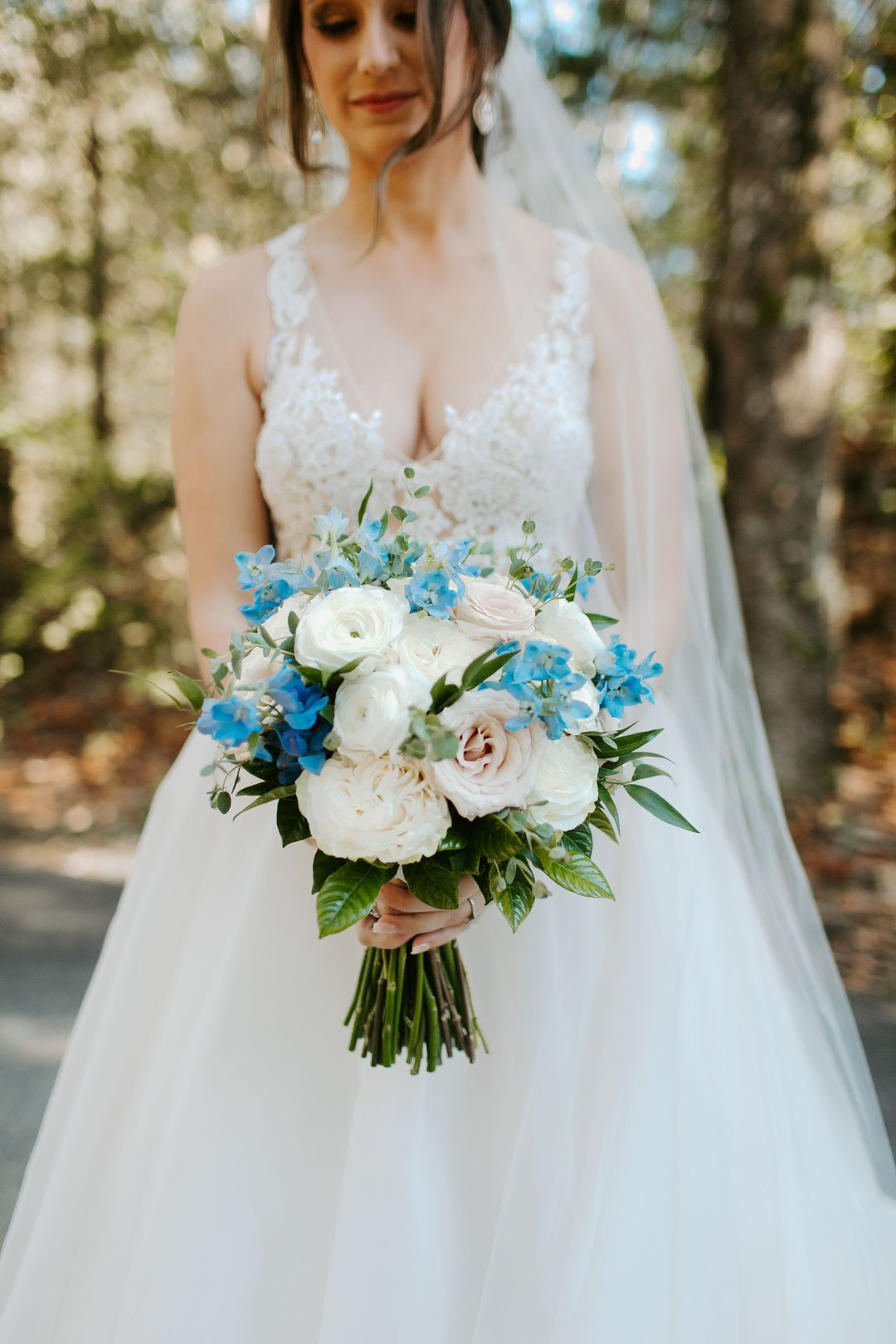 white and blue wedding, bride holding bouquet with white hydrangeas, blush roses and blue accent blooms