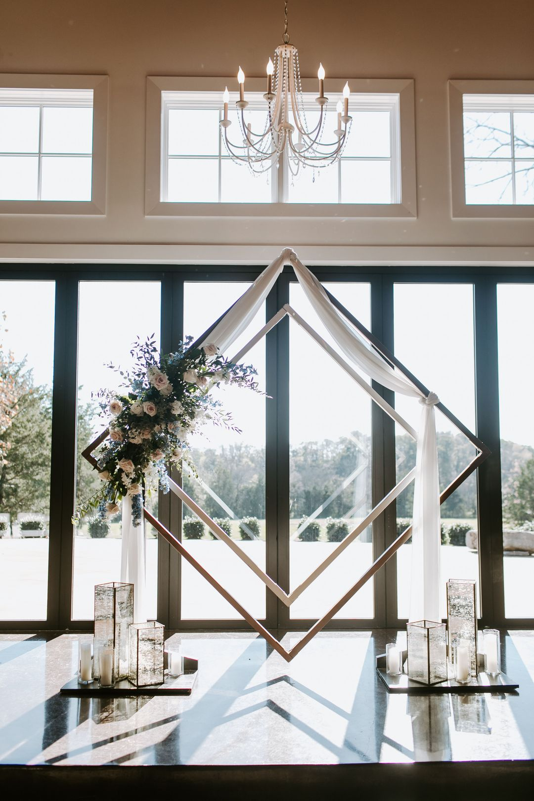 geometric wedding altar installation with candles and flowers