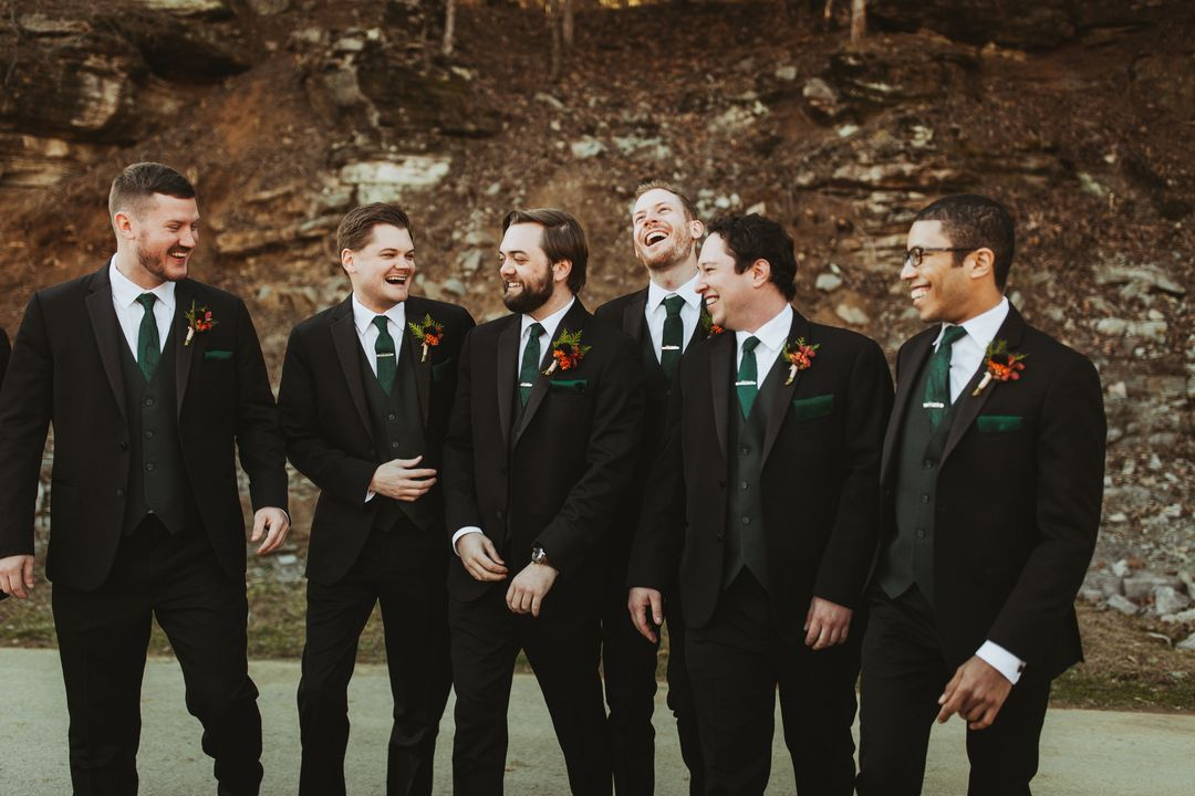 black and emerald groomsmen suits with red boutonierres