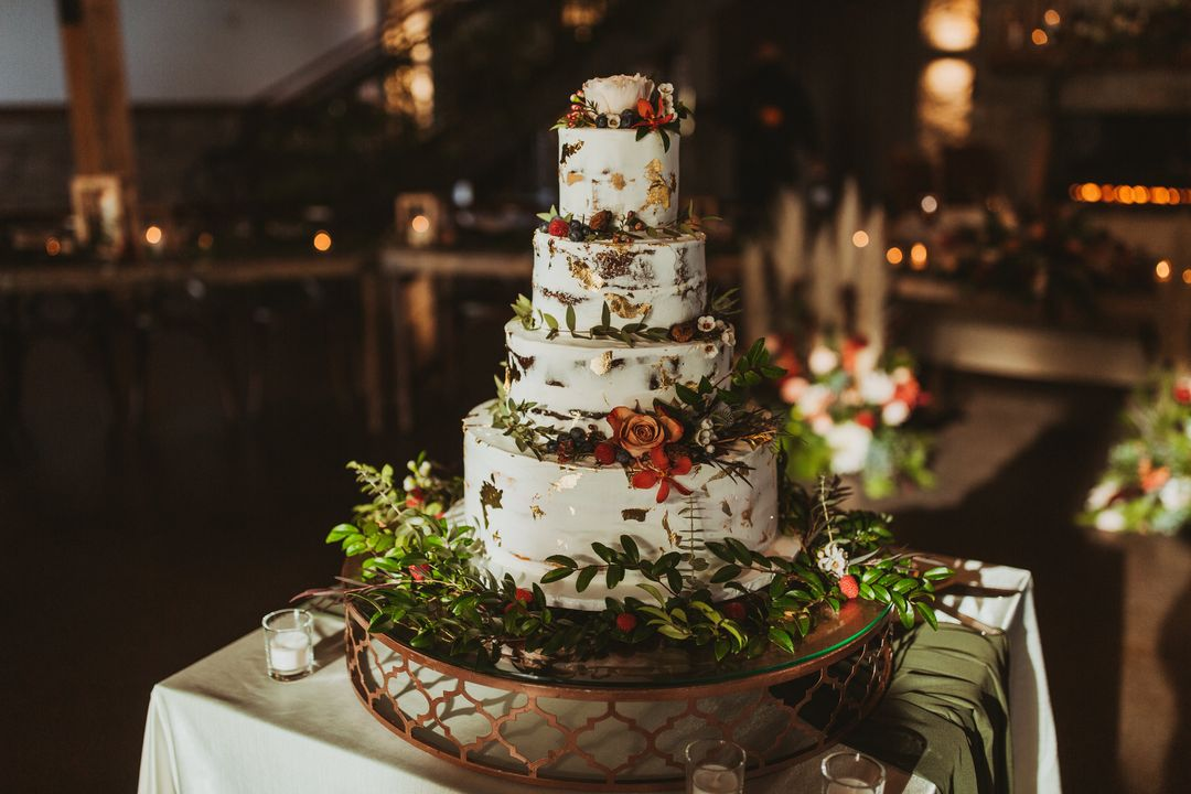 white wedding cake with green and red flowers