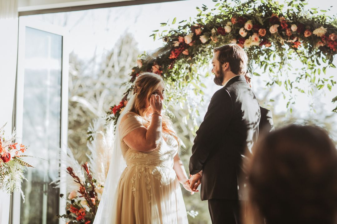 bride cries at wedding ceremony, round floral arbor