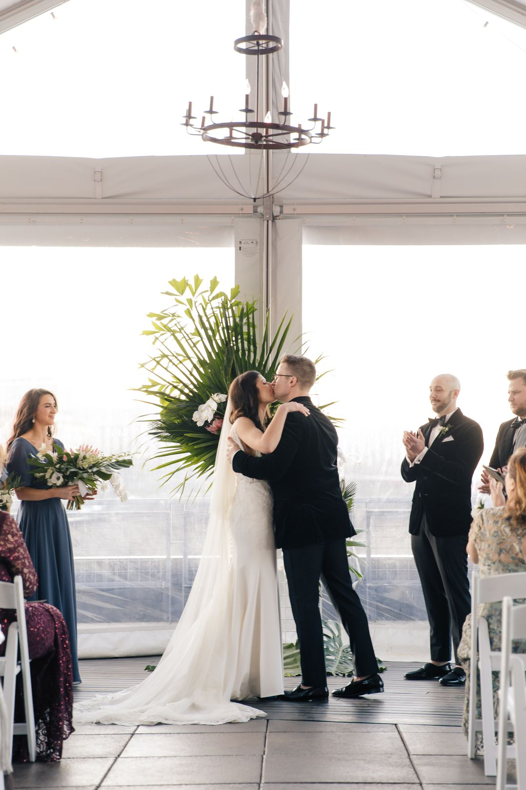 bride and groom kiss, tropical themed wedding at the bridge building