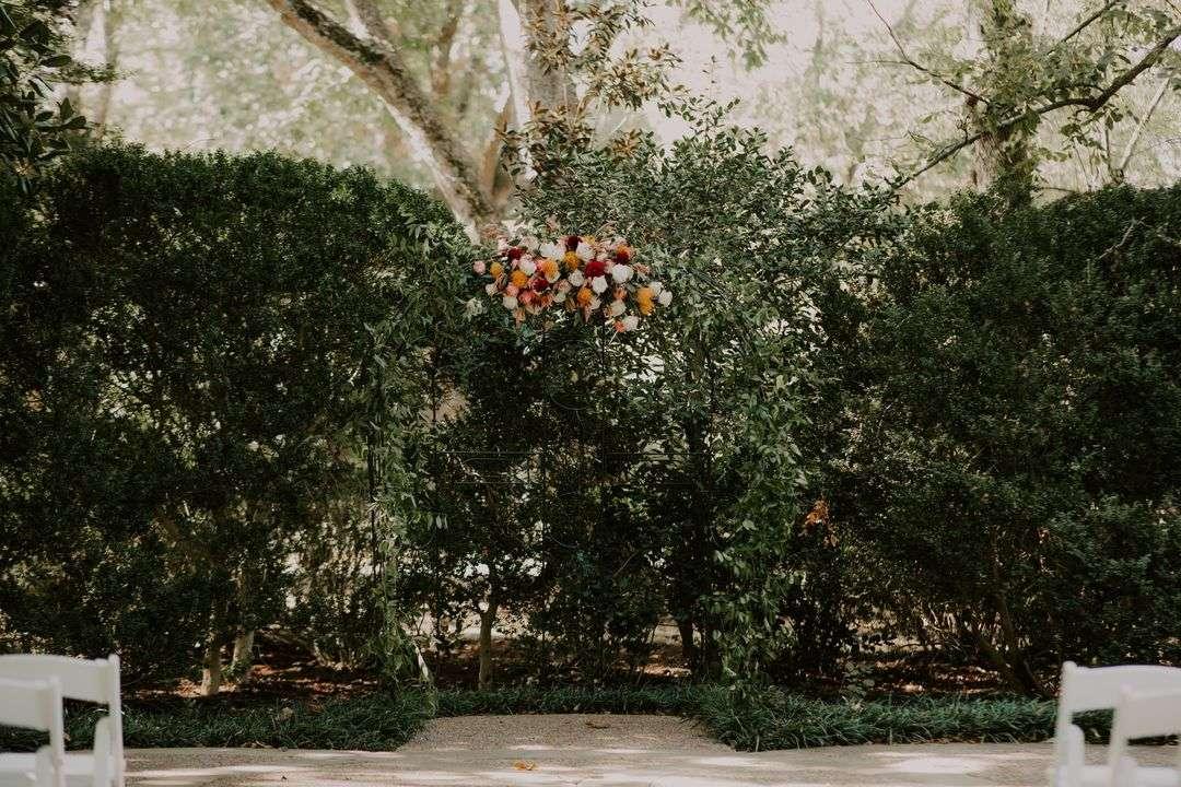 orange and red wedding ceremony flowers on arbor