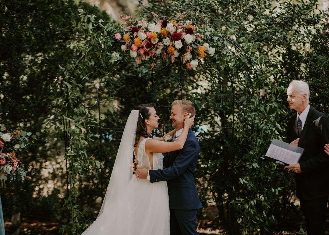 bride and groom wedding ceremony arbor flowers