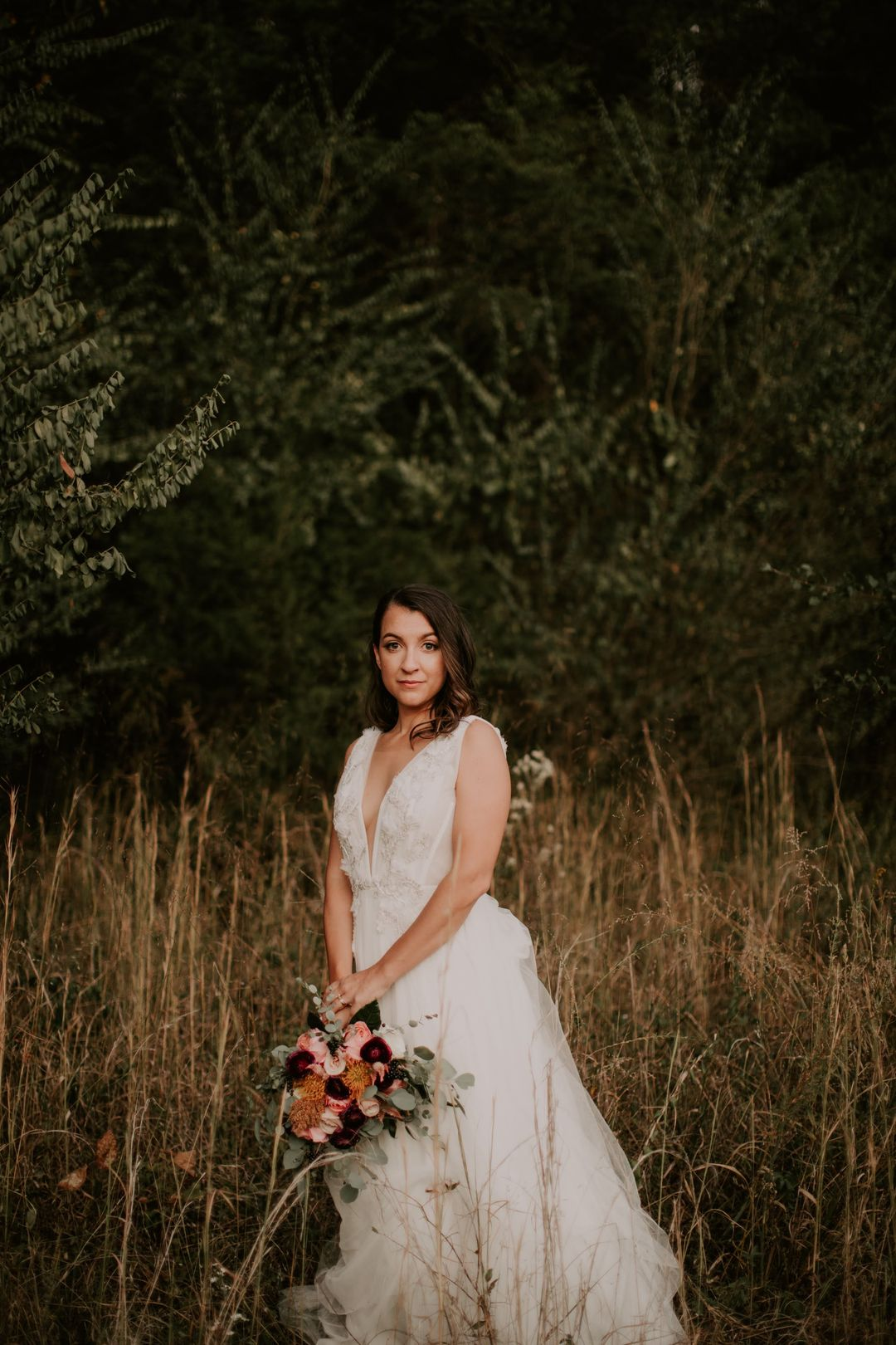 aline wedding dress and orange and red bridal bouquet