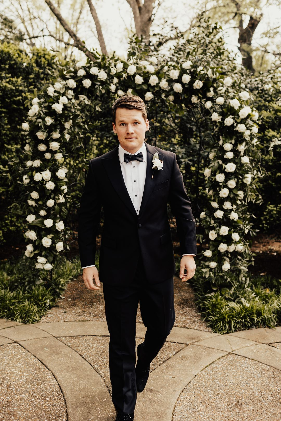 groom in black tux with white boutonierre