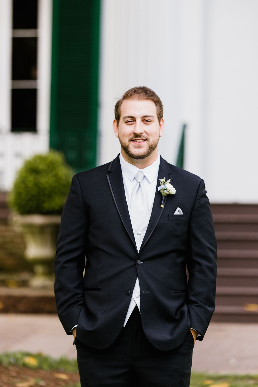 groom in black suit with white boutonierre
