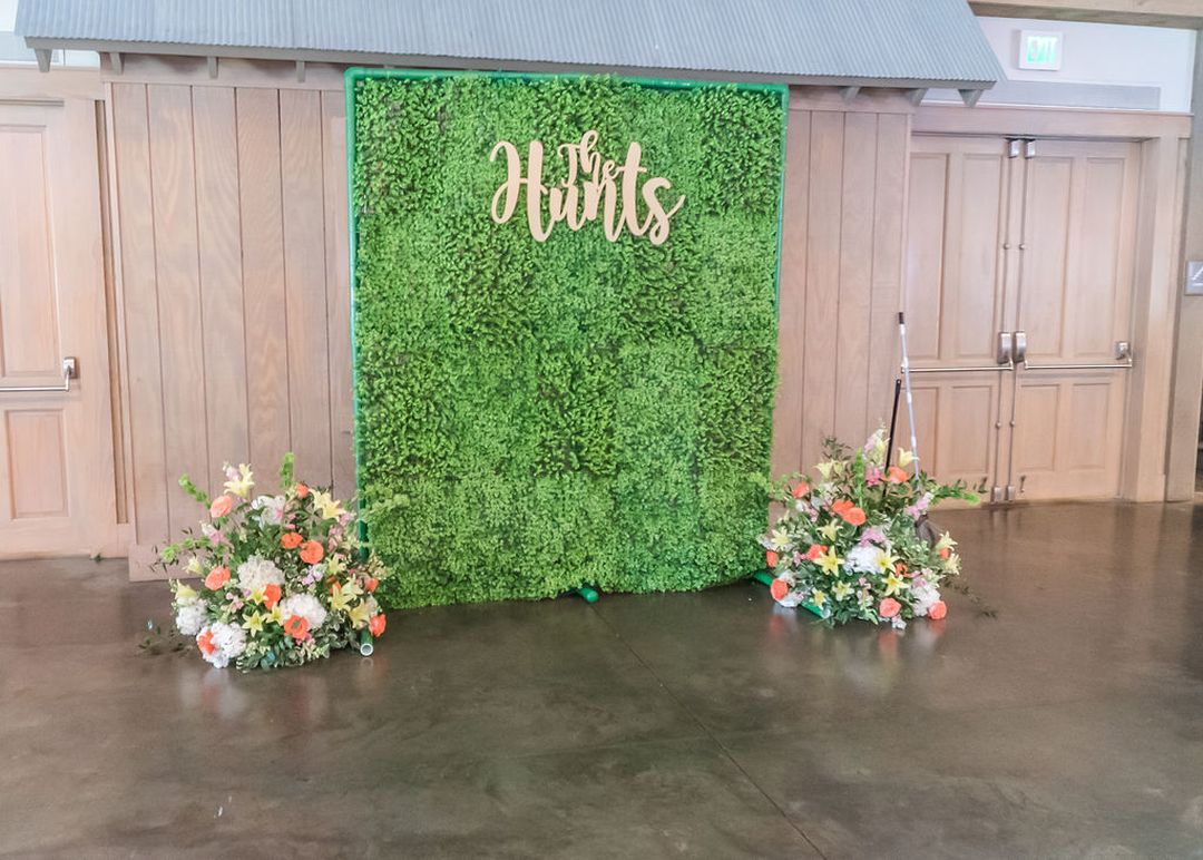 grass wedding backdrop, yello and pink flowers